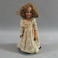 """Kammer & Reinhardt/Simon & Halbig Open-mouth Bisque Head Doll, c. 1920s, back of head incised """"K*R Simon & Halbig 117 n"""" with sleeping blue glass eyes, open mouth with two inset teeth, curly blonde mohair wig, five-piece jointed composition toddler body, cream linen dress and black leatherette booties, ht. 18 in."""