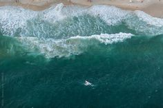 ocean from above with surfer by HOWL for Stocksy United