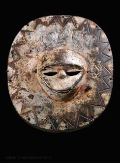 """A superb Eket circular wooden mask - round mask panels used during Ekpo secret society ceremonies. This very fine and large example has a whitened, deeply-layered, thick patina. It is made from a medium heavy wood and measures 15"""" in height, 12.50"""" at its widest point and 4""""in depth. From coastal Nigeria, early 20th century."""