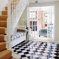 Hallway with black and white chequered floor tiles, white chaise longue and sisal staircase runner
