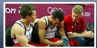 201b: In this picture there are two athletes and one coach. The picture is just a thumbnail and so facial details are difficult to identify. The mood of the picture is low. One athlete appears to be crying and is being comforted by his teammate. The athlete's nationality is not recognisable from the photograph