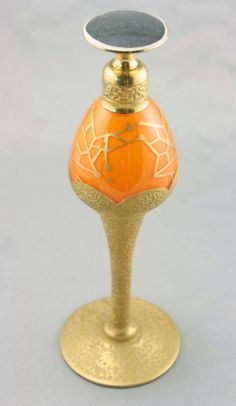 "DeVilbiss art deco dropper top perfume bottle, 1926, 7"" tall, reverse painted body in vivid orange decorated with scalloped gold encrusted gleaming gold motif and matching stem and foot. The body is also adorned with a hand painted vibrant gold geometric deco design. The original hardware is embossed with a deco scroll pattern and the dropper top is finished with a glossy jet black disc insert. The original glass dauber is intact. Signed on the bottom, Made in USA, DeVilbiss. (hva)"