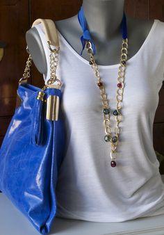 Bolso de piel y collar de bisutería con lazo de seda natural y cristales de colores.Ambos del Salón Rosa.