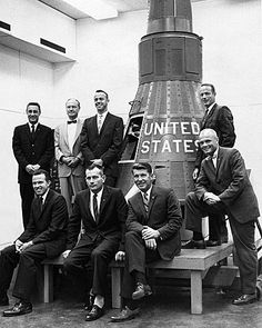 Original seven U.S. astronauts pose next to their spacecraft, Project Mercury.  John Glenn, front right is the only one still living in 2014.  Top row in bow tie appears to be Flight Director Chris Craft.