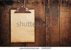 Old clipboard on grungy wooden surface, with plenty of copy space. - stock photo