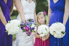 I LOVE how the bridesmaids are in bold colors with white flowers in their bouquets and the bride in white has all the colors of the bridesmaids dresses in her bouquet!  It's gorgeous!