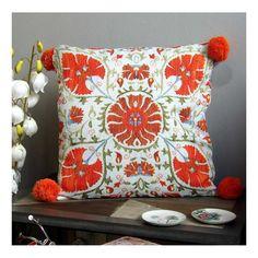 Cojín de cama o sofá de formato cuadrado de 45x45 cm en tonos azules y naranja, con pompones en las esquinas. Desenfundable.