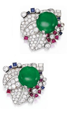 A Pair of Art Deco Platinum, Jade, Coloured Stone and Diamond Clip-Brooches, Cartier, London, Circa 1935. Each centring a button-shaped jade cabochon, within a foliate surround set with baguette, old European and single-cut diamonds, further decorated with calibré-cut rubies and sapphires, both signed Cartier London. #Cartier #ArtDeco #ClipBrooch