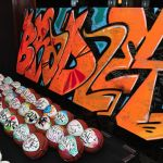 Put a new twist on personalized favors with the Simon Elliot Events Graffiti Studio. Your guests have their choice of personalized graffiti phone and iPod cases, fitted hats, or authentic miniature leather sports balls, created on the spot by New York's leading graffiti artists.    The Graffiti Studio comes stocked with:    The latest mobile phone and iPod cases  Flat brimmed fitted hats in a variety of colors  Miniature leather basketballs, footballs, soccer balls, and baseballs