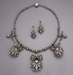 AN ANTIQUE DIAMOND NECKLACE/TIARA--The old-cut diamond collet line suspending three graduated diamond fringe clusters and two smaller pendants to the plain silver beaded backchain, clusters detach, with fittings for brooches, hatpins, and a tiara, with a pair of earrings en suite, mounted in silver and gold, circa 1860.