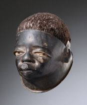 Mozambique, Makonde  light-weighted wood, dull black patina, real hair, showing realistic facial features, the lip plug is a female attribut...