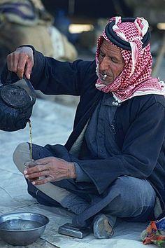 Bedouin man smoking a cigarette, preparing tea, Syria, Middle East