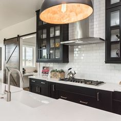 You love black cabinets but you also feel that you need to open up space and let it breathe more?  Glass fronts on your black kitchen cabinets are a great option to open up your kitchen space and, at the same time, introduce contrast. And, you'll also provide some space for all those pretty possessions to display.  📷 by Gardner Homes  #blackcabinets #blackcabinetry #blackktchen #blackkitchencabinets #blackkitchens #blackkitchendesign #blackkitchendecor #glassfrontcabinet #paintedcabinets Black Kitchen Decor, Black Kitchen Island, Black Kitchen Cabinets, Kitchen Cabinet Design, Black Kitchens, Glass Front Cabinets, Upper Cabinets, Wood Storage Cabinets, Timeless Kitchen