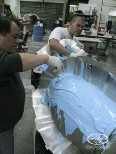 At Stan Winston Studio, special effects character creators Gary Yee and Chris Cheatham brush silicone onto HULK's giant leg during the mold making process.