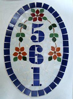 Numero residencial em mosaico, tamanho oval pequeno (30x20). Cliente pode escolher cor da borda e do número. O mosaico é realizado em cima de um piso de ceramica e deverá ser fixado na parede com argamassa. Ou poderá ser feito 2 furos para parafusar na parede a pedido do cliente.