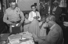 Not originally published in LIFE.Two girls stand with their mother as she is questioned by an officer and Arizona Attorney General Ross Jones (seated) after the 1953 Short Creek raid.