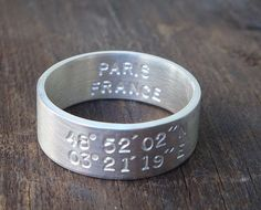 A simple, hand-stamped sterling silver ring, with the latitude and longitude coordinates of your choice on the outside and on the inside is the city (or anything else of your choice).  By artist Allison Cecil.  Brilliant. Latitude And Longitude Coordinates, Silver Stacking Rings, Sterling Silver Rings, Everyday Rings, Custom Stamps, Wedding Locations, Metal Bands, Band Rings, Wedding Ring