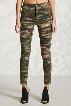 A pair of mid-rise pants featuring an allover camo print, distressing, a five-pocket construction, and a zip fly.