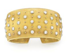 A DIAMOND AND GOLD CUFF BRACELET, BY BUCCELLATI   The wide hinged 18k gold cuff set with collet-set diamonds, mounted in 18k gold, 2¼ ins. diameter, 1 3/8 ins. wide  Signed Buccellati, Italy, no. F4570