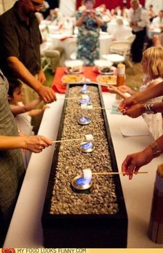s'mores station for a party. Sterno burners in a planter box with rocks. YES!!!