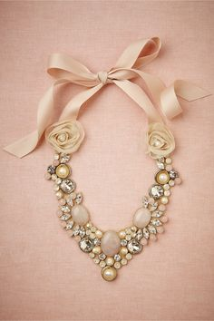 """Rose Trove Necklace from BHLDN Embedded on taffeta, smooth cabochons of rose quartz, pearls, and faceted crystals are tied 'round your neck with soft pink ribbons. Due to their handmade nature, color may vary slightly. Handmade by Ranjana Khan. Tie closure. 20""""L, 1.5""""W ties; 13""""L, 2.5""""W embellishment. Glass crystals, brass, base metal, rose quartz, organza, cotton ribbon, taffeta backing. Imported."""
