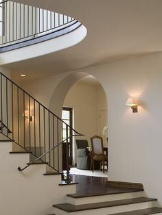 clean iron rail (love how it dies into the wall without continuing with the balusters) | sconces | stairs/floors