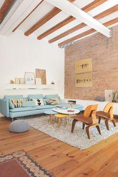 Salón con sofá azul, mesa de centro con diferentes alturas y colores, alfombras y sillas de diseño