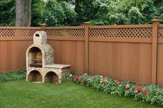 clôture en PVC, barbecue en pierre et parterre de fleurs