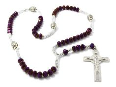"""Purple with Silver Tone 30"""" Glass Beaded Chain Jesus Rosary Cross Pendant with Charms Necklace. Chain Length: 30 Inches. Cross Dangle Length: 6 Inches. Total Length : 36 Inches. Cross Pendant Measurements (Length x Width): 2-3/4"""" x 1-7/8"""". This item is not real Silver."""