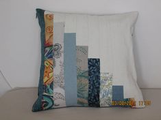 This stylish patchwork cushion cover is made from various furnishing fabrics in shades of green/blue. The back is blue and corresponding strips are made from cream furnishing fabric. It has a 41 cm nylon zip. The patchwork side of the cushion is lined with cotton fabric. It requires a