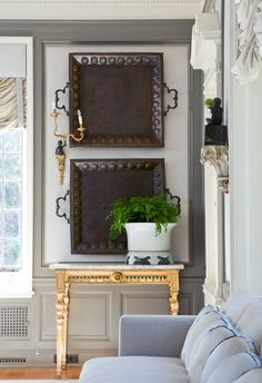 Eclectic room. I love the iron trays displayed on the focal wall.