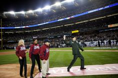 Retired Army Capt. Tony Odierno, a West Point graduate and Yankees employee who lost his arm in Irag,throws the first pitch,as First Lady Obama and Dr.Jill Biden ,and Yogi Berra look on at the beginning of Game 1 of the World Series at Yankee Stadium,in Bronx,N.Y.10/28/2009.