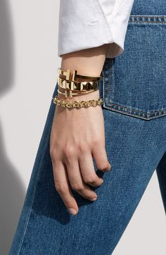 """""""Always find that balance,"""" stylist Vanessa Traina says of mixing graphic gold bracelets with a button-down and blue jeans. """"It is classic yet modern with an edge…it makes a statement that is both bold and at ease."""""""
