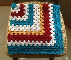 This is a generously-sized modern take on the traditional granny square afghan! It was crocheted using a white with primary colored tweed