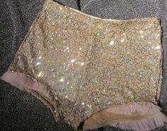 Gold Sequin shorts hot pants with tulle edge. Stretchy pull on with elasticated top. 94% Nylon, 6% Elastane  HOT PANTS SIZE CHART  - UK…