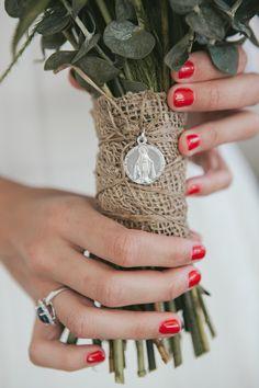 Detalle de la boda de Marta, en Galicia, con medalla religiosa prendida en su ramo con arpillera. En argyor.es podrás encontrar charms, cruces y medallas perfectas para personalizar tu ramo de boda en diy tan bonitos como éste.
