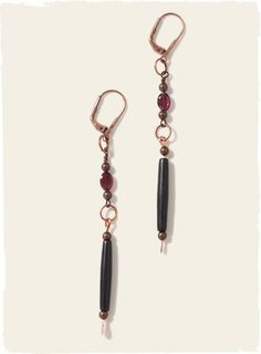 The understated earrings are polished black horn and faceted garnet on copper links. Leverback clasp.