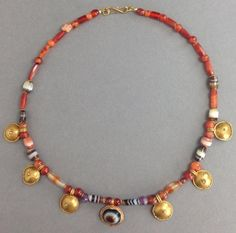 An ancient Roman necklace comprised of gold shields, banded sardonyx, carnelian, and amethyst beads with modern gold clasp Ca. 1st -4th century AD. Overall length: 17 in. (43 cm). Intact and wearable.