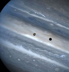 Io Casts Shadow on Jupiter. The three snapshots of the volcanic moon rounding Jupiter were taken over a 1.8-hour time span. Io is roughly the size of Earths moon but 2,000 times farther away. In two of the images, Io appears to be skimming Jupiter's cloud tops, but its actually 310, 000 miles (500,000 kilometres) away. Io zips around Jupiter in 1.8 days, whereas the moon circles Earth every 28 days.