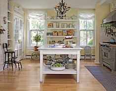 The kitchen gets farmhouse appeal by incorporating from open shelving and scattered antiques, but the crystal chandelier adds an elegant touch.