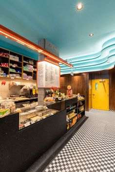 Combining refreshments and a retail display, this main bar emphasises Caffettiera Caffé Bar's social focus and curves down to meet the checkerboard mosaic floor.