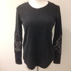 Black top with lace cutout on sleeves. Has a nice quality almost sweater feel to the fabric (96% polyester 4% spandex). Lace is 89% nylon 11% spandex. Also available in Small and Large. Tops