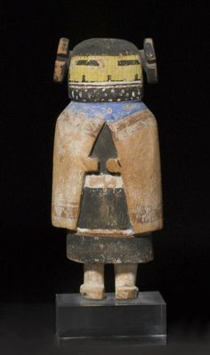 A Hopi kachina doll  Representing A-Ha Kachina mana, fashioned from a single block of wood, separate maiden's whorls, the diminutive relief-carved hands emergent from the correspondingly executed manta.  height 12 1/2in