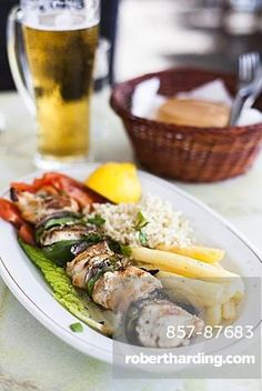 Grilled chicken kebab and a pint of beer at a restaurant in Greece.