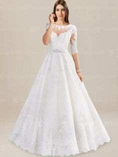 Vintage wedding dress brings a unique beauty and elegance that you love. It features an illusion top with elbow length lace sleeves. The bodice is heavily accented with beaded lace appliques. Natural waist is accented by a beaded satin belt. Back is complete with a chapel length train with scalloped edge.