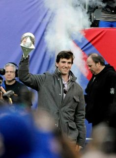 Giants quarterback Eli Manning walks onto the field with the Vince Lombardi Trophy during a rally at MetLife Stadium on Tuesday, Feb. 7, 2012, in East Rutherford, N.J. The Giants defeated the New England Patriots in the NFL football Super Bowl on Sunday. (AP Photo/Bill Kostroun)