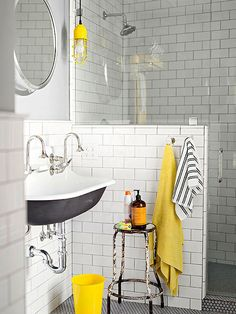 Classic white subway tile mixes with vintage finds, such as the old farm stool and a refurbished wall sink. The underside of the sink is painted a matte black, while yellow and black accents dot the room! http://www.bhg.com/bathroom/color-schemes/colors/bathroom-color-schemes/?socsrc=bhgpin010415blackyellowhitebathroom&page=3