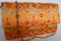 carteira nellfernandes em cetim francês floral com fundo laranja. Tamanho: 23 x 15. R$130,00.