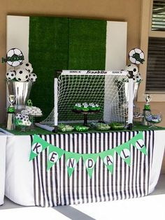 Table setup for a soccer birthday party or a World Cup party, complete with trophies, soccer balls, and a goal! #Soccer #SoccerParty #Futbol #FutbolParty #WorldCup #WorldCupParty #SoccerPartySetup #Sports #SportsParty #SportsTheme #SoccerTheme