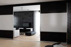 Contemporary sliding room dividers, double sided in white and black glass with anodised silver aluminium frame.